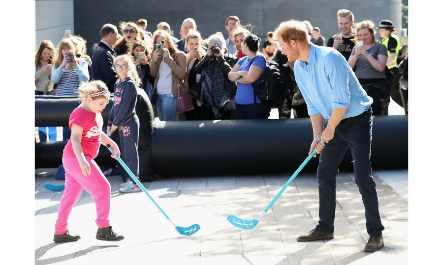 Let the games begin! Harry faced off against a little girl in a friendly game of street hockey. 