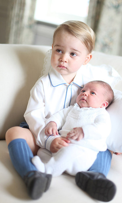 The little Prince proudly held on to his baby sister, while sitting on a couch, for their first portraits together.