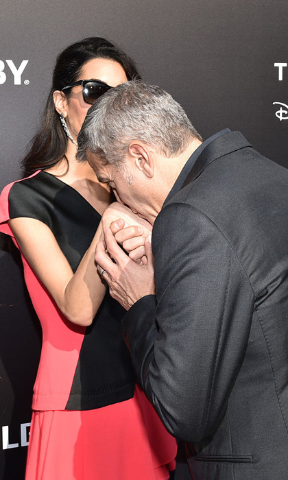 A kiss for his lady! George showed off what a gentleman he is at the premiere of Disney's <i>Tomorrowland</i>.