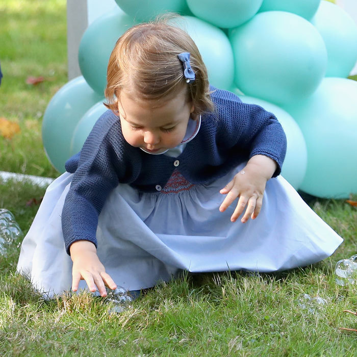 Queen Elizabeth's great-granddaughter played with bubbles in the grass.