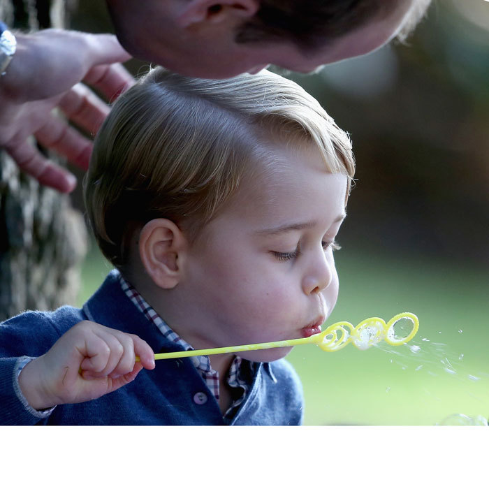 William gave George a gentle stroke on the head as the little Prince blew bubbles at a children's party in Victoria, Canada.
