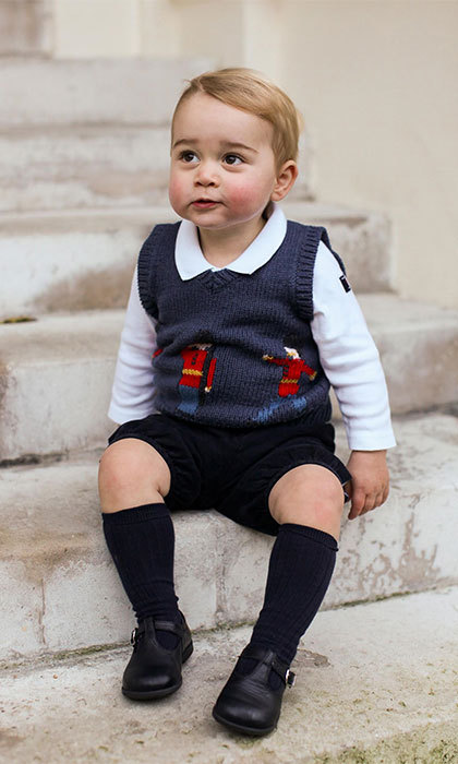 George looked dapper and ready for the holidays in Christmas photos wearing a navy sweater by British designer Cath Kidston that featured royal guards, along with a white collared top by Sweden's Polarn O. Pyret, black shorts and matching high socks.