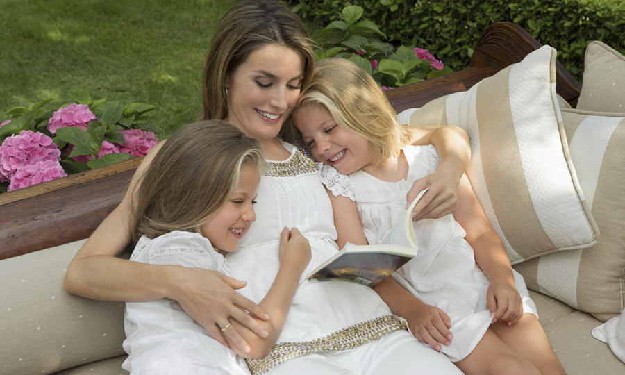 Letizia cuddled close to her daughters at their home in Madrid.