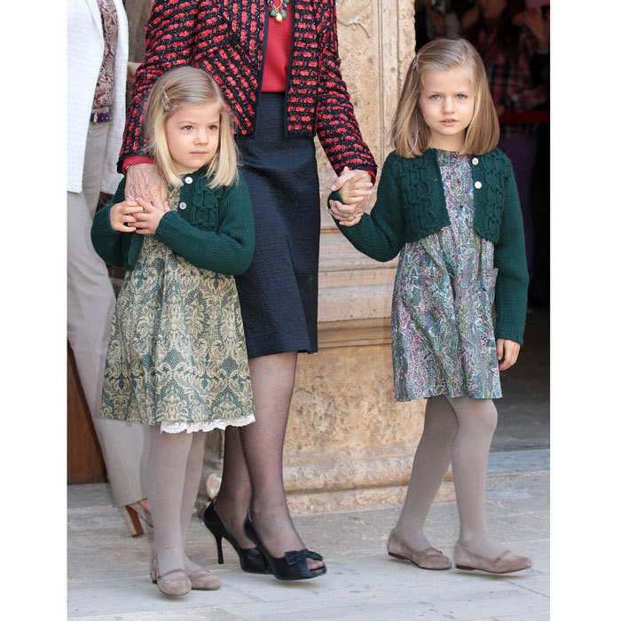 Queen Letizia's daughters showed off their twinning style wearing matching green cardigans and tights paired with printed feminine frocks during Easter 2012 services.