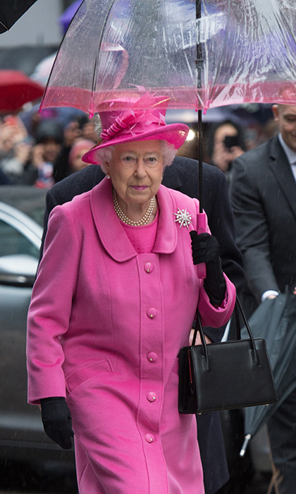 Queen Elizabeth matched her umbrella to her bubblegum-hued ensemble for a visit to Birmingham.