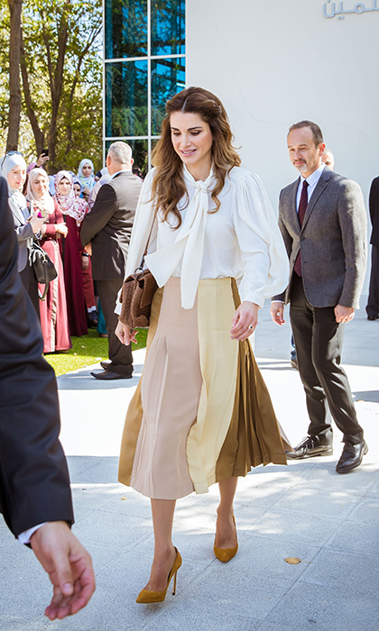 Queen Rania of Jordan looked sophisticated and chic in this color block pleated midi and pussybow blouse.