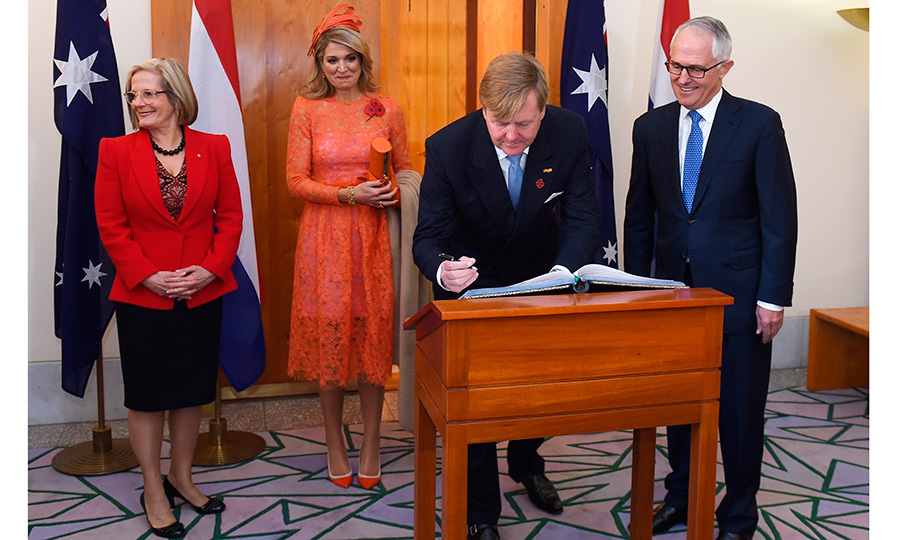 Joined by Australia's Prime Minister Malcolm Turnbull, right, and his wife Lucy, left, Queen Maxima donned a coral orange lace dress for the signing of the visitors' book at Parliament House in Canberra. 