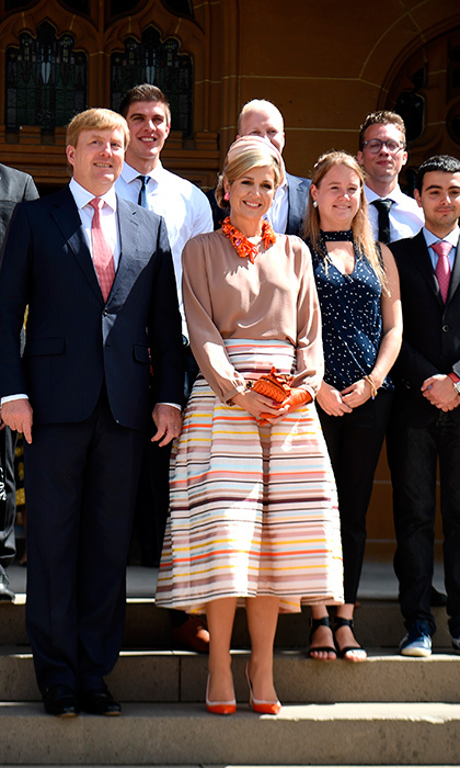 Queen Maxima was a ray of sunshine in her colorful pleated skirt, accessorized with bright orange statement jewelry as she met with students during a visit to the University of Sydney.