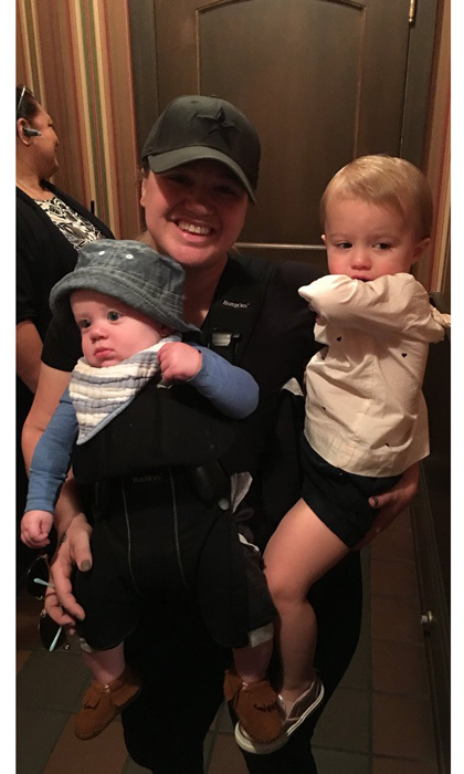 Kelly Clarkson looked like any other mom as she toted her son Remy on her chest and carried her daughter River Rose Blackstock with one arm during their family trip to Disney World.