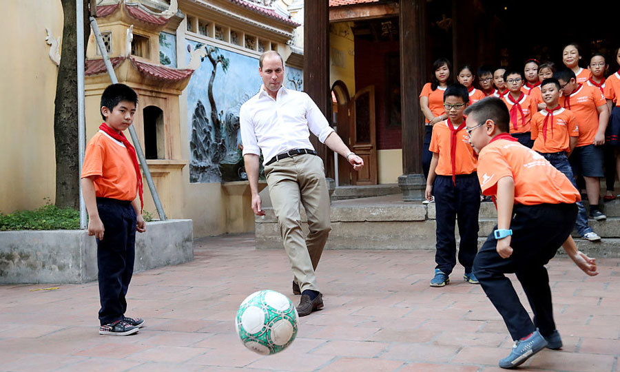 Bend it like Beckham! The Prince showed off his soccer skills, playing a game with students at a local school on Lan Ong Street.