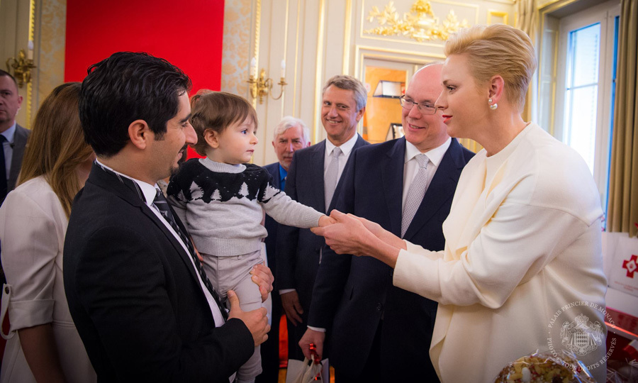 Prince Albert's wife shook hands with a young boy, while at the Red Cross headquarters in Monaco, where the royals were passing out parcels at the annual charity ceremony.