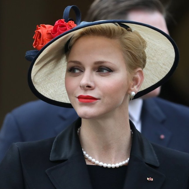 Princess Charlene's red lips matched the roses adorned on her hat for the National Day of Monaco celebrations.