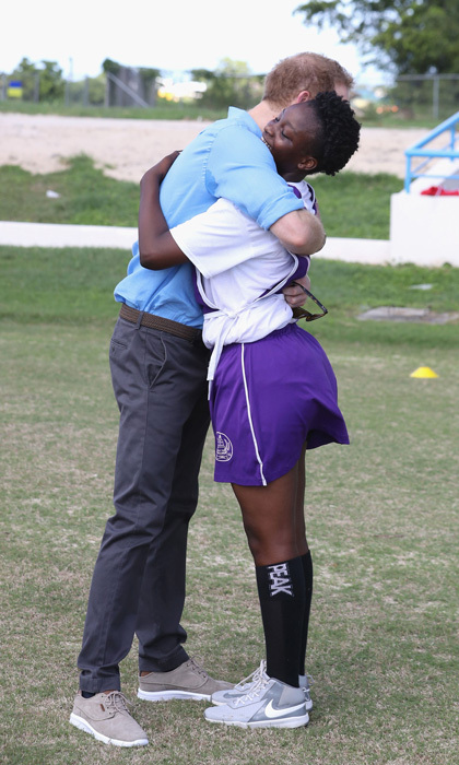 Prince Harry opened his arms to a young girl at a youth sports festival at the Sir Vivian Richards Stadium in Antigua during his royal tour of the Caribbean.  