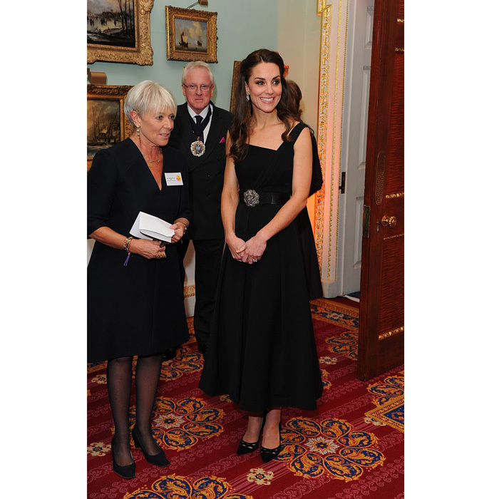The British royal looked elegant on November 22, donning a blacksatin midi dress by Preen, which features an asymmetric neckline, to the 201 Place2be Awards in London. Kate completed her evening look wearing her tresses up in a half-up 'do and accesorizing the frock with a Temperley London crystal bow belt and suede Prada pumps.