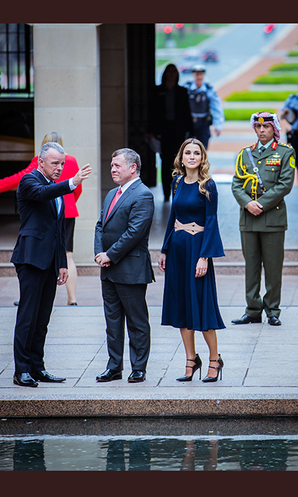Queen Rania was characteristically stylish in a deep blue pleated dress with statement sleeves and belt. 