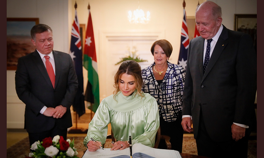 As King Abdullah and Australia Governor General Sir Peter Cosgrove, joined by wife Lynne, looked on, the Queen signed a guest book during a ceremony at the Government House in Canberra on November 22.