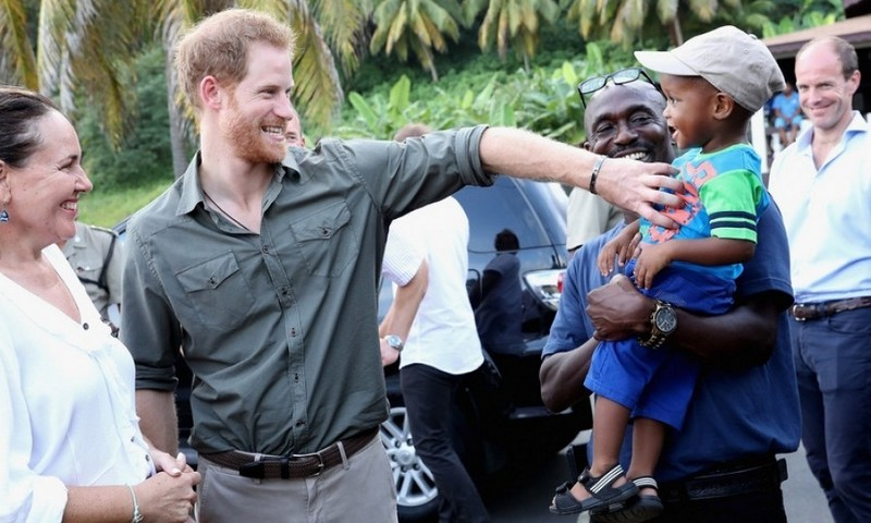 Tickle, tickle! Prince Harry couldn't help but get a laugh out of a boy named Jyasi Junior as he visited a Turtle Conservation Project.