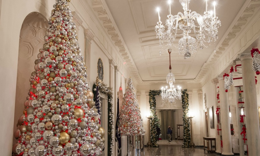 Cross Hall is lined with trees decorated with gold and silver ornaments. 