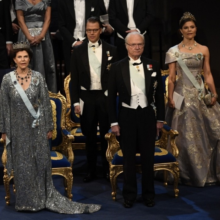 The Swedish royal family sparkled at the Nobel Prize banquet in Stockholm on December 10. Queen Silvia matched her sparkly dress to the Leuchtenberg tiara. Meanwhile, her oldest daughter Crown Princess Victoria chose a one-shouldered metallic dress.