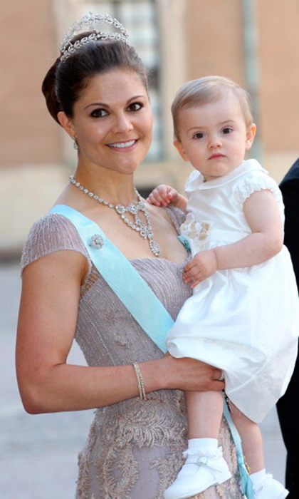 Why wear just one wreath of diamonds when you can wear two? Princess Victoria smiles holding daughter, Princess Estelle in a vintage two-tier tiara.