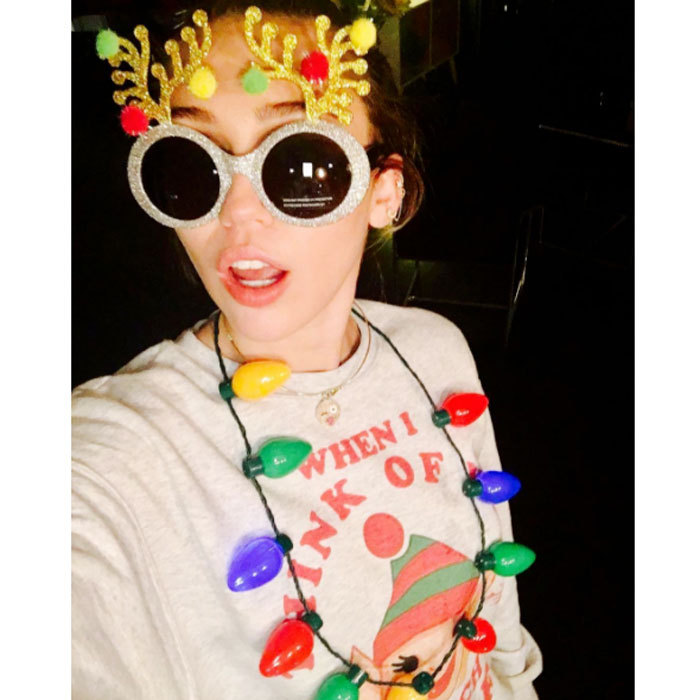 "Miley Cyrus showed off her Christmas spirit donning festive holiday wear in a photo she captioned, ""It's startin to look a lot like you know what.""