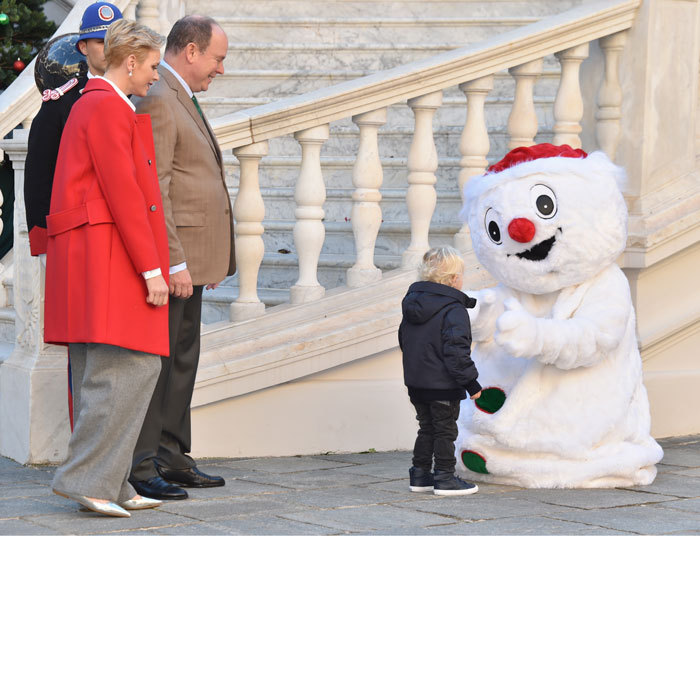 The little Prince happily greeted a Santa hat-wearing snowman as his parents looked on.