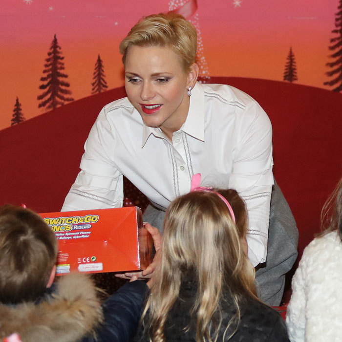 Princess Charlene was the picture of elegance wearing a Carolina Herrera pleated button-front blouse and pearl drop earrings to pass out toys to kids.
