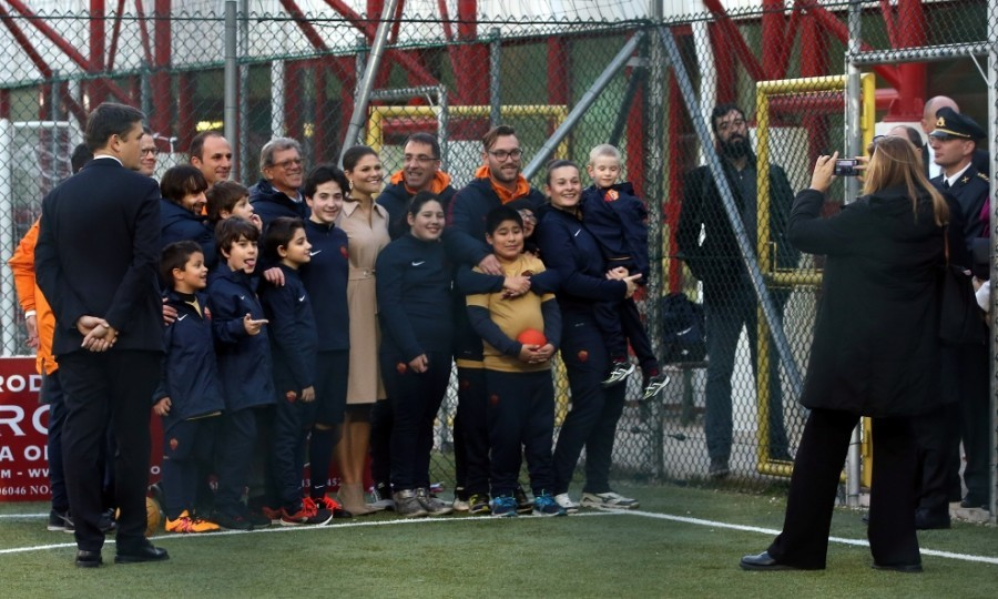 Crown Princess Victoria of Sweden posed for a picture with children and Minister Ekstrom visit AS Roma soccer club at the St. Peter's Pontifical Oratory in Rome, Italy. 