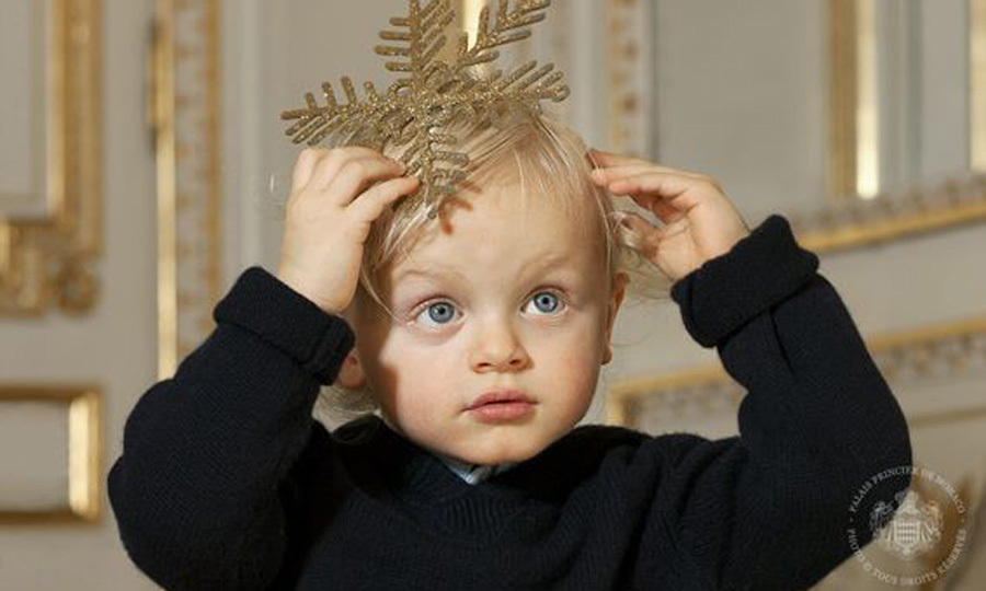The young Prince looked angelic playing with a Christmas decoration during his family's holiday photo session.