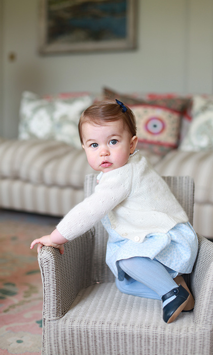 Princess Charlotte was wide-eyed and on the move in her first birthday portraits taken by her mother Kate Middleton. The Princess, who turned one in May, took a series of snaps at Kensington Palace, which show her posing in a chair and pushing her scooter through the lawn. 