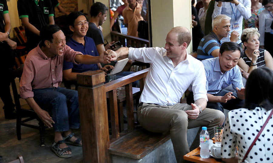 William shook hands with an excited local during his visit to Vietnam's Aha cafe, where the royal was joined by conservation supporters.