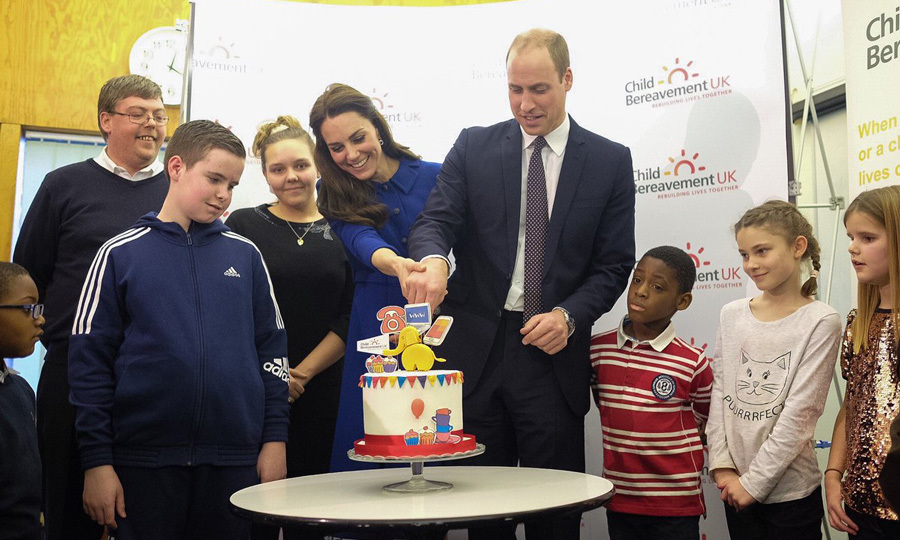 The Duchess gave her husband a hand as they cut a colorful cake in honor of the London Centre's one-year anniversary.