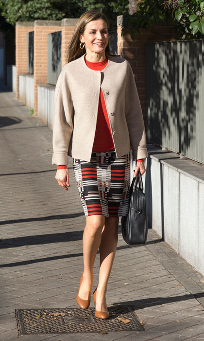 Queen Letizia showed off her chic street style donning a  BOSS tweed skirt, which she paired with a vibrant red BOSS wool sweater and beige jacket as she made her way to a meeting with the board of directors of the Spanish Federation of Rare Diseases.