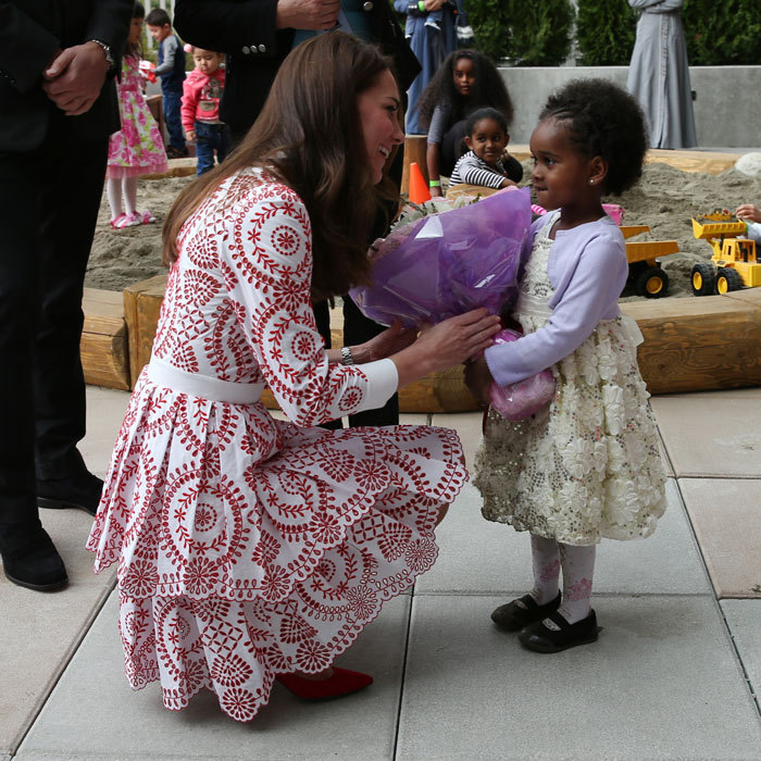 Prince George's mom graciously accepted a bouquet of flowers from a young girl during her visit to the Immigrant Services Society of British Columbia New Welcome Centre in Vancouver, Canada. 
