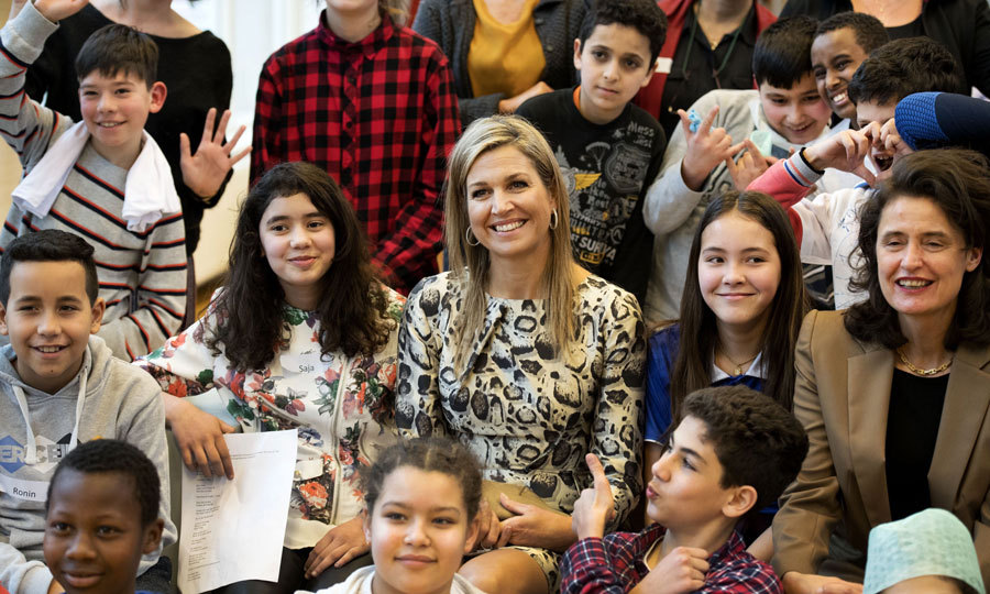 Queen Maxima of the Netherlands was all smiles as she posed with children during a visit to the IMC Weekend school in Haarlem.