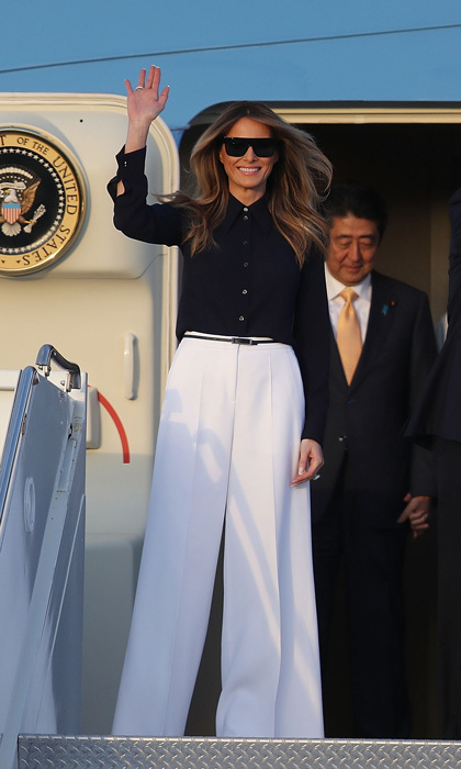 First Lady Melania Trump disembarked Air Force One with Japanese Prime Minister Shinzo Abe at the Palm Beach International Airport wearing high-waisted, white wide-legged Michael Kors pants paired with a black button-front blouse.