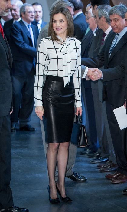 Queen Letizia of Spain was business chic wearing a black leather skirt and a checkered pussybow blouse by Roberto Verino for the El Valor Economico del Español conference in Madrid.