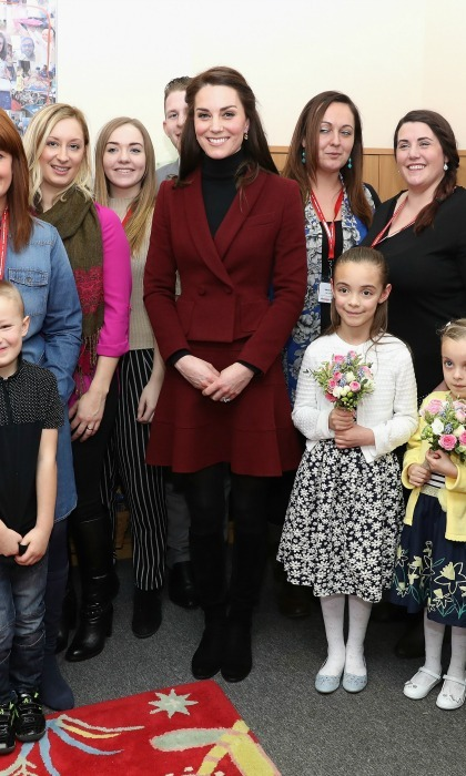Kate Middleton wore a burgundy peplum double-breasted skirt suit by Paule Ka during her engagements with Action for Children in Wales. 