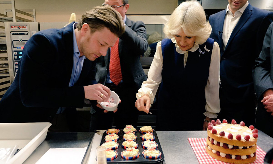 The Duchess of Cornwall put her culinary skills to the test as she launched the Great Get Together challenge. Prince Charles' wife joined celebrity chef Jamie Oliver for a baking session at the Clarence House kitchen decorating  cupcakes.