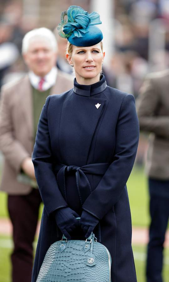 Queen Elizabeth's granddaughter Zara Phillips matched her navy coat with a blue hat and purse at the Cheltenham festival in England. 