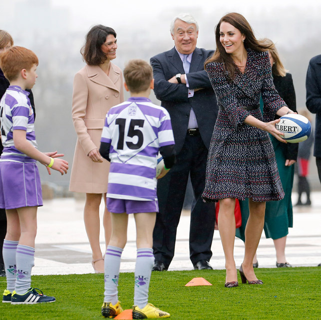 Catch! Sporty Kate showed off her rugby skills as she took part in a drill with some local children.