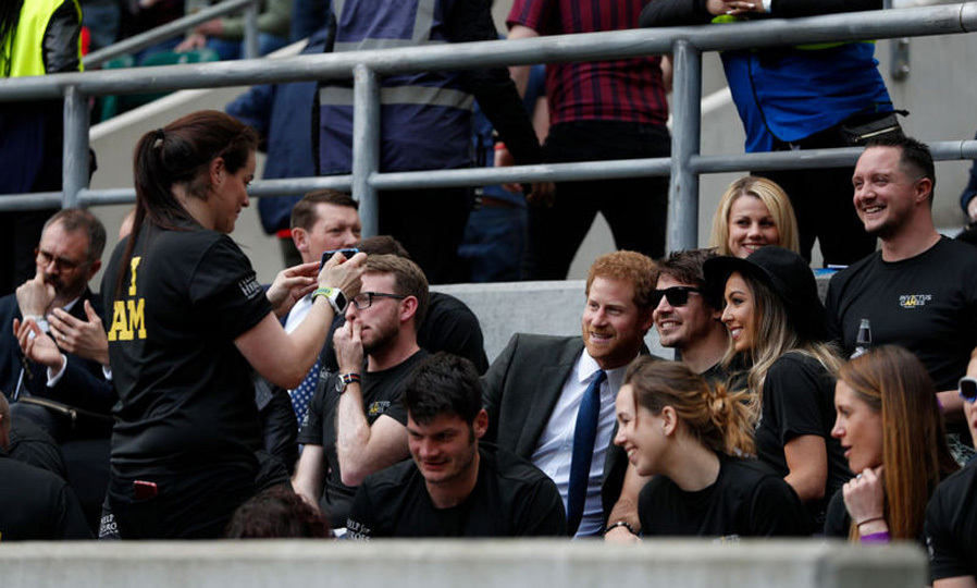 Prince Harry then stepped in front of the camera for a photo with with competitors from the 2014 and 2016 Invictus Games who were also watching the Army Navy rugby match.