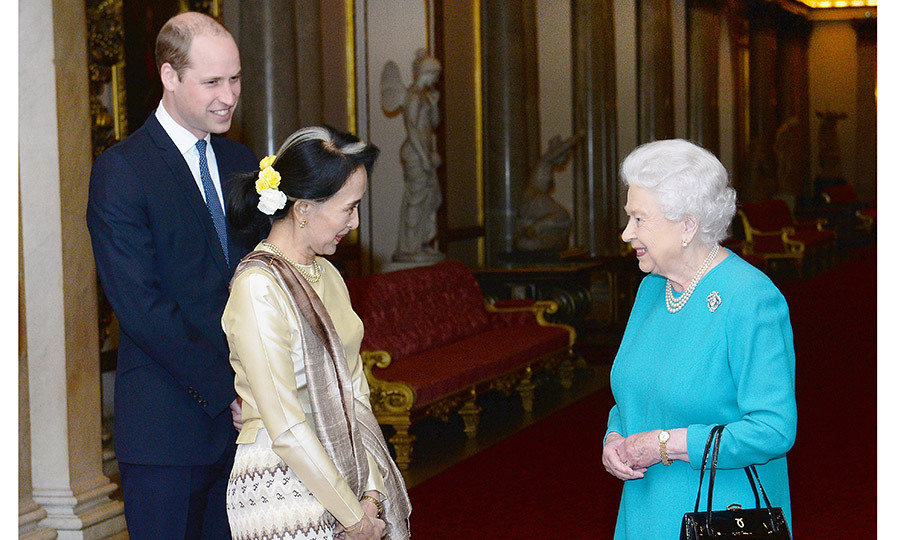 One day after his grandfather revealed plans to step down from his royal duties, Prince William joined grandmother Queen Elizabeth II to greet Aung San Suu Kyi ahead of a private lunch at Clarence House on May 5.