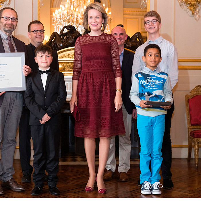 Belgium's Queen Mathilde wore a burgundy dress with lace overlay as she joined recipients of the Queen Mathilde Prize, left to right, Toon Beelaerts, Florian Lievens, Johannes Lievens and Kamiel Put at the Royal Palace in Brussels. 