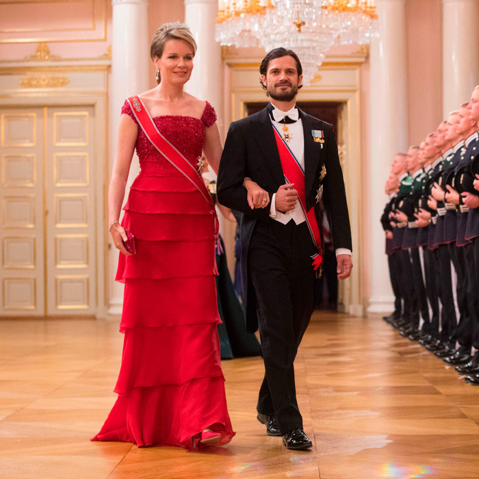 Queen Mathilde, who was escorted by Prince Carl Philip, wore a tiered red gown to the first night of King Harald and Queen Sonja's joint birthday celebration in Oslo.