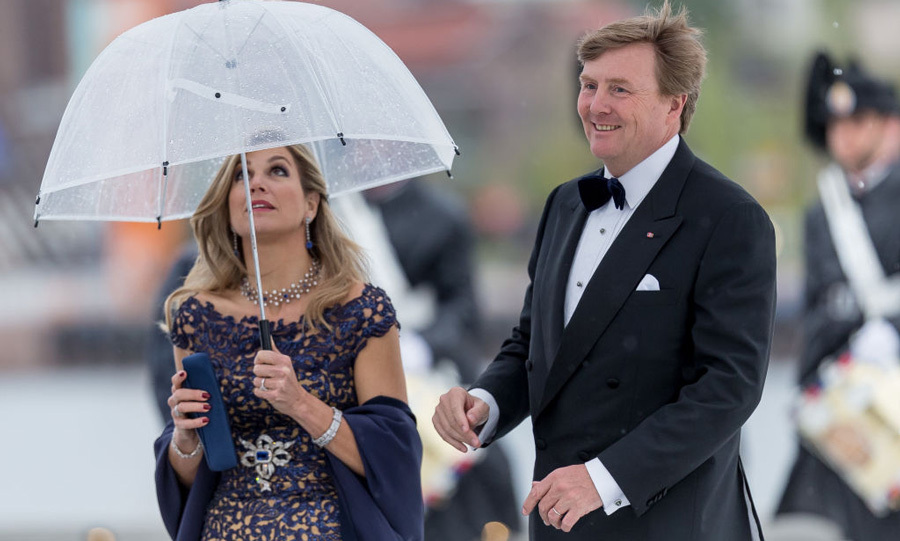Queen Maxima made sure her umbrella was protecting her gorgeous navy gown as King Willem-Alexander braved the wet weather.