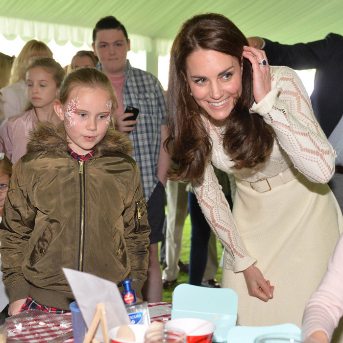 The Duchess managed to keep her light yellow See by Chloe dress spot-free as she checked out the arts and crafts station at the tea party.