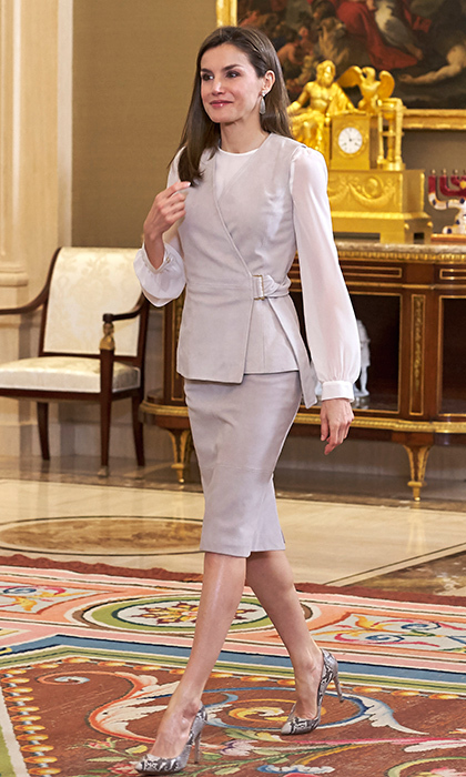 Queen Letizia of Spain attended audiences at Zarzuela Palace wearing this modern look – a sheer blouse and belted asymmetrical vest with matching pencil skirt by BOSS. Adding a touch of the wild side: the royal's Magrit snake print heels. 