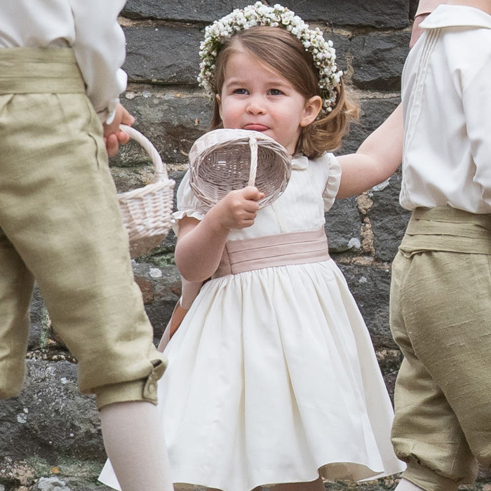 Charlotte stuck out her tongue as she held on tight to her flower basket ahead of walking down the aisle in front of her mom, dad, and family.