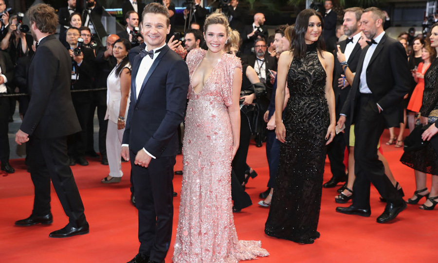 Jeremy Renner and Elizabeth Olsen, who wore a sequin gown with a plunging neckline, attended <i>Wind River</i> premiere.
